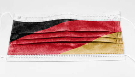 The national flag of Germany printed on a disposable surgical mask. Coronavirus covid-19 pandemic prevention and protection. Health and medicine
