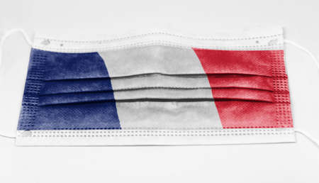 The national flag of France printed on a disposable surgical mask. Coronavirus covid-19 pandemic prevention and protection. Health and medicine Stock Photo