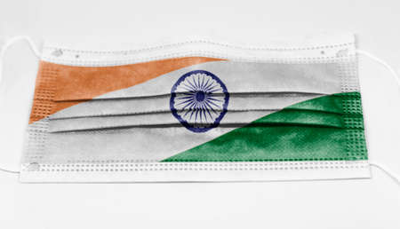 The national flag of India printed on a disposable surgical mask. Coronavirus covid-19 pandemic prevention and protection. Health and medicine