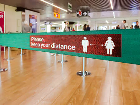 Green ribbon barrier inside an airport with the warning to maintain social distancing due to the pandemic of Coronavirus