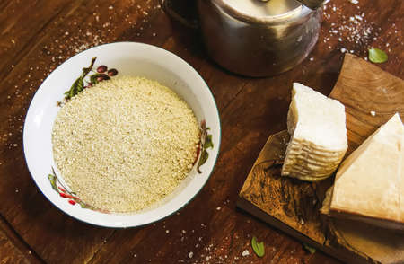 Grated cheese in a ceramic bowl on a rustic wooden board. Traditional Italian cuisine. Stock Photo