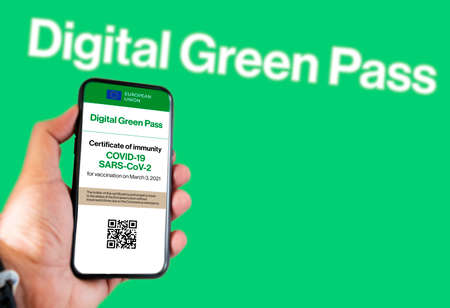 The digital green pass of the european union with the QR code on the screen of a mobile held by a hand with a blurred green background. Immunity from Covid
