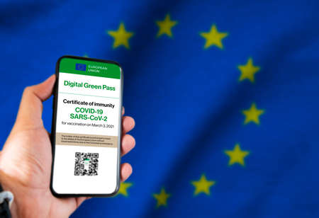 The digital green pass of the european union with the QR code on the screen of a mobile held by a hand with a blurred EU flag in the background. Immunity from Covid Reklamní fotografie