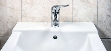 Chromed faucet with lever to mix hot and cold water on a modern white sink in a bathroom with tiled walls. Domestic life and hygiene