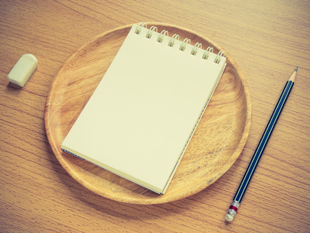 commentator: Paper note on wood dish with pencil and eraser, Concept for Menu Creation or Restaurant Commentator, Vintage Filter process.