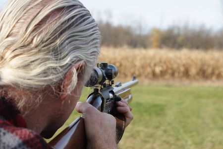 marksman: Hunter Aiming a Gun Stock Photo