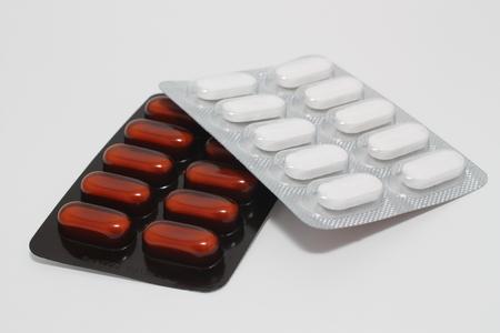 Two packs of pills on a white Фото со стока