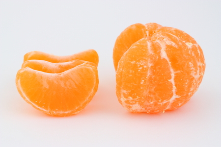 separated: Peeled mandarin with three separated slices on a white Stock Photo