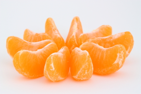 A few slices of mandarin on a white