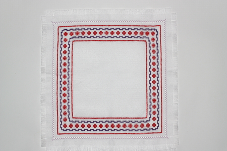 Embroidery with a geometric pattern of red and purple colors