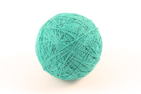 Ball of green yarn on white