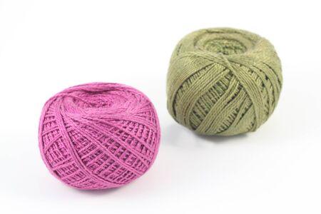Two green and purple balls of yarn on white Фото со стока