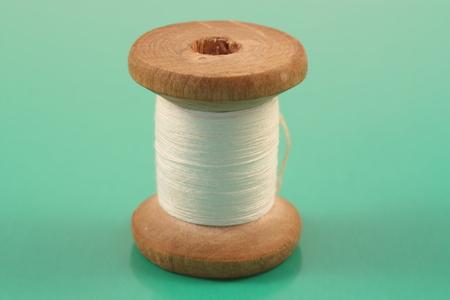 Spool of white thread on a green Фото со стока