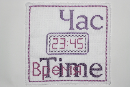 Embroidery depicting clock in purple
