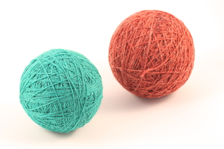 Two green and red balls of yarn on white