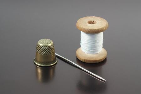 Old needle, thread and thimble on gray Фото со стока