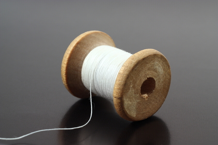 Spool of white thread on a gray