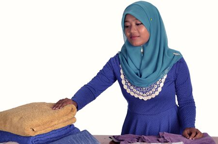 Young muslim lady arranging laundered clothes isolated in white background photo