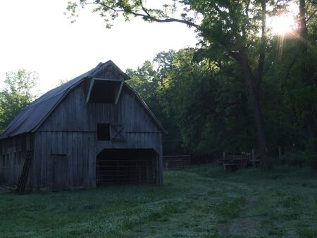 Barn; old barn on farmranch at sunrise with rays of light shinning