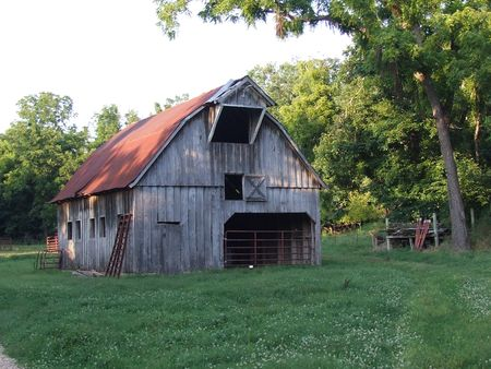 old barn; historic weathered old barn with red roof Stock Photo