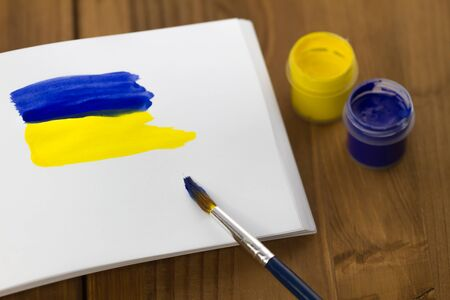 sketchbook: Painted Ukrainian flag on sketchbook with colorful paint tubes and brush on wooden background
