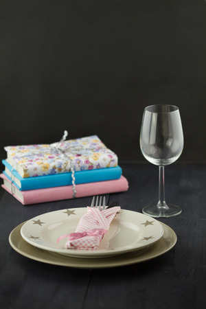 Table setting: plate, fork, knife, pink napkin, glass with stack of books on dark wooden table photo