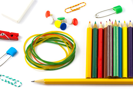Closeup school supplies: colored pencils paper clips pencil sharpener stationery gum small clothespin colored pins pencil isolated on white background photo