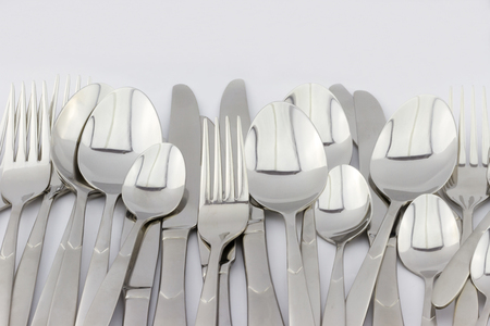 Heap of silver forks spoons and knifes on white background Stock Photo