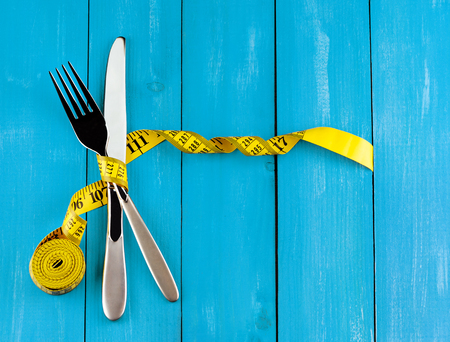 Healthy lifestyle concept. Top view of silver fork and knife with yellow measuring tape on blue wooden background