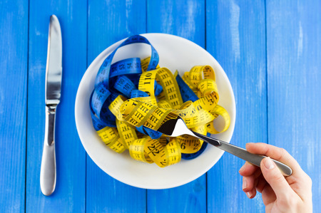 Healthy lifestyle concept. Top view of female hand holding fork with measuring tape over the plate on blue wooden background