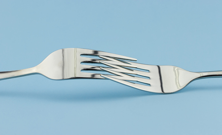 Closeup of two silver fork isolated on blue background