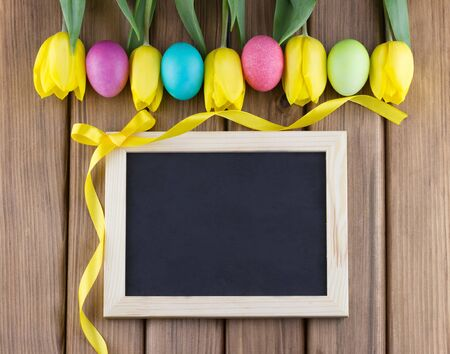 Happy Easter concept.Top view of yellow tulips with colorful painted Easter eggs and blank blackboard with curly ribbon on wooden background Stock Photo