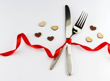 Concepto Cena romántica. Vista superior de tenedor y cuchillo de plata decorada cinta roja con arco y corazones de madera sobre fondo blanco con el lugar para su texto Foto de archivo - 41428596