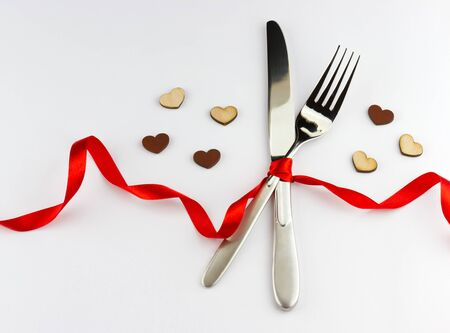 Romantic dinner concept. Top view of silver fork and knife decorated red ribbon with bow and wooden hearts on white background with place for your text