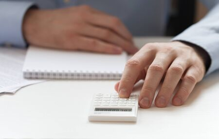 Concepto de negocio. Los hombres de negocios en la calculadora y sentado en la mesa con el cuaderno Foto de archivo - 41428580