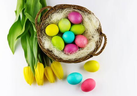 Happy Easter concept. Top view of yellow tulips with basket full of colorful painted Easter eggs on white background Standard-Bild