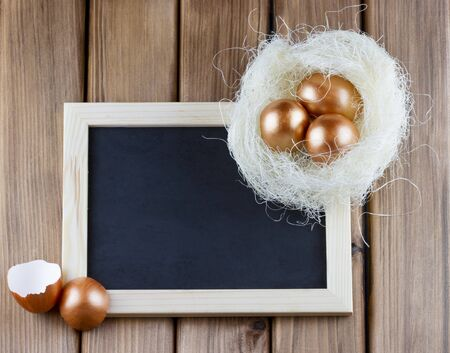 Happy Easter concept. Top view of blank blackboard with golden eggs in the nest on wooden background
