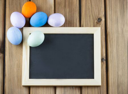 Happy Easter concept. Top view of blank blackboard with colorful Easter eggs on wooden background