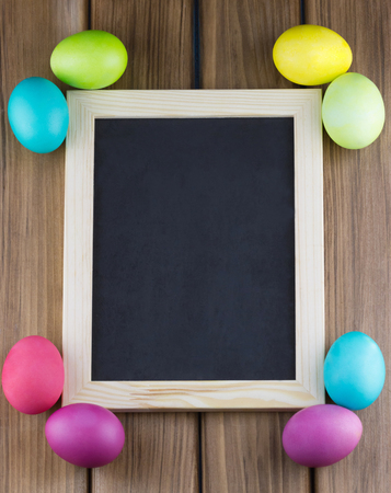 Happy Easter concept. Top view of blank blackboard with colorful Easter eggs in the corners on wooden background Standard-Bild
