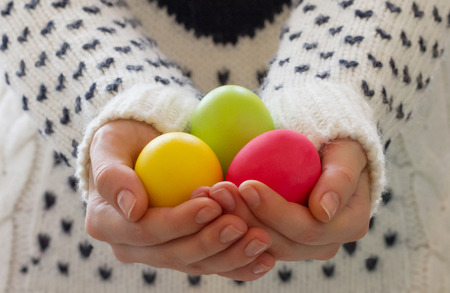 Happy Easter concept. Female hands holding colorful Easter eggs