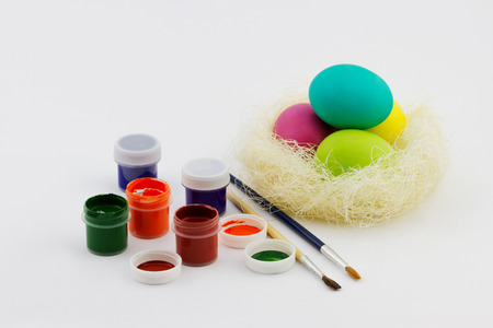 Happy Easter concept. Clorful painted Easter eggs in the nest with tubes and brush on white background
