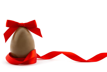 Happy Easter concept. Chocolate easter egg decorated red ribbon with bow isolated on white background with place for your text