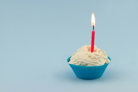 Happy birthday cupcake with pink burning candle on blue background