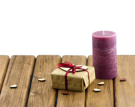 Purple candle with gift box and hearts on wooden background photo