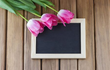 Pink tulips with empty blackboard on wooden background