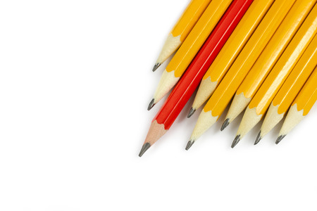 One red pencil standing out from the row of yellow pencils isolated on white background Standard-Bild