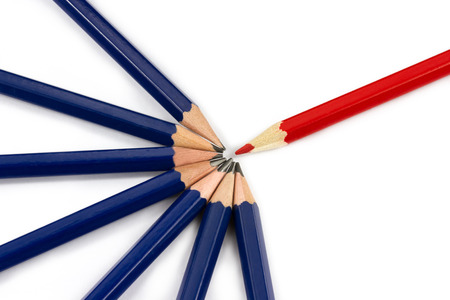One red pencil standing out from the circle of dark blue pencils isolated on white background