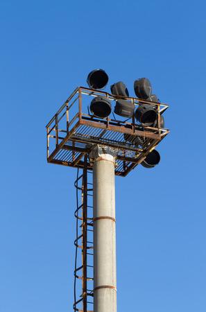 Old broken spotlights pillar in stadium on blue sky background