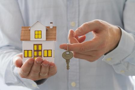 banco dinero: Concepto de la hipoteca. Empresario la celebración de la casa de juguete en una mano y las llaves en el otro lado