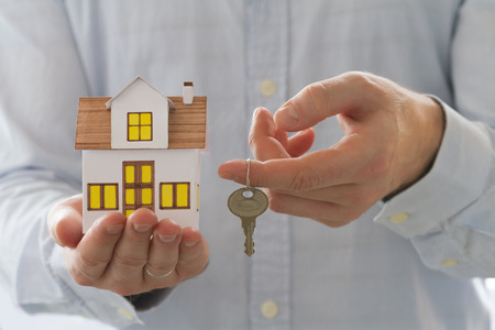 Mortgage concept. Businessman holding toy house in one hand and keys in the another hand